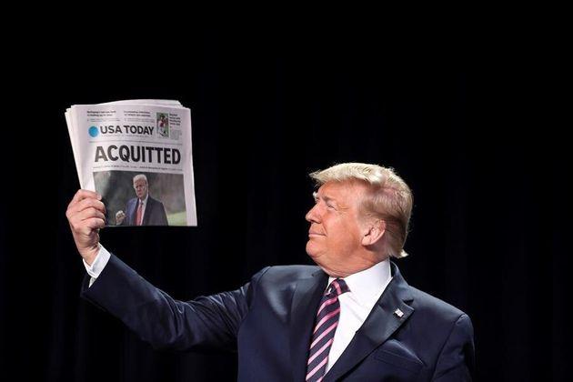 Donald Trump sujeta un periódico tras librarse del primer impeachment, en febrero de