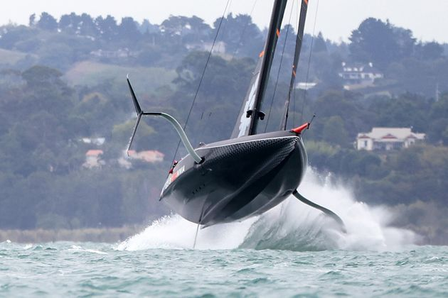 AUCKLAND, NEW ZEALAND - FEBRUARY 14: INEOS Team UK flies into the air against Prada Luna Rossa during...