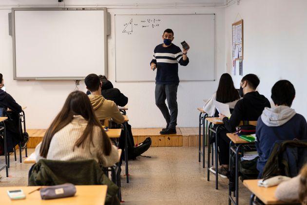 Un profesor da una clase en un instituto en A