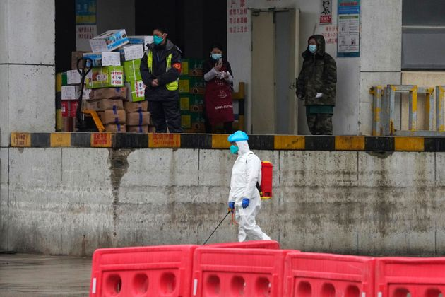 A worker in protective overall passes by a warehouse at the Baishazhou wholesale market during a visit...