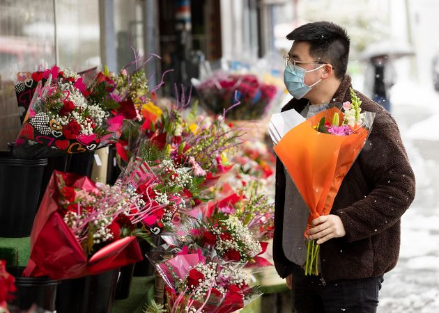 A man wearing protective face mask buys flowers at Trafalgar Food Market & Flowers store on Valentine's...