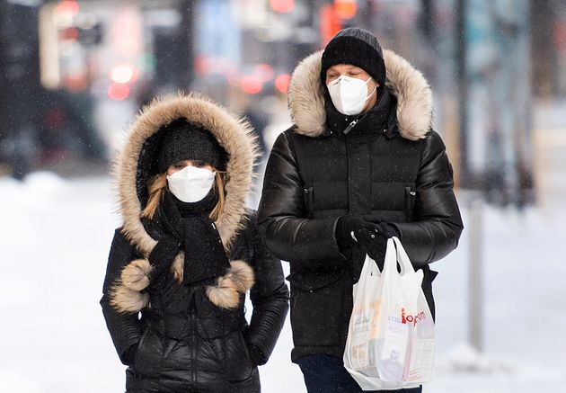 People wear face masks as they walk along a street in Montreal on Jan. 23,