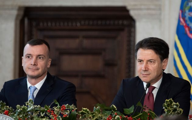 Italy's Prime Minister Giuseppe Conte (R), flanked by his spokesman Rocco Casalino (L), speaks during...