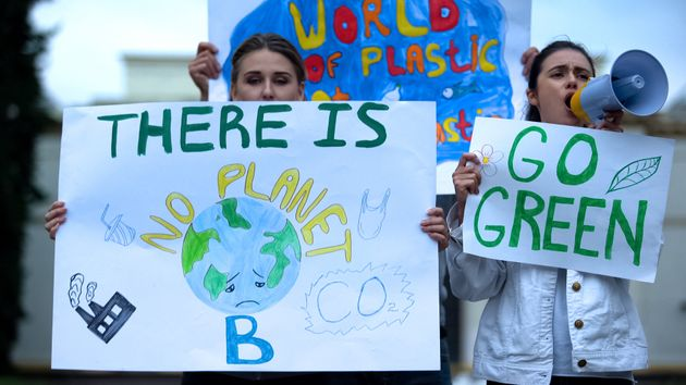 Ecologists with banners shouting in megaphone about pollution, global