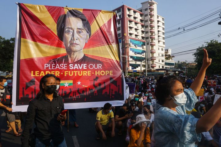 A banner featuring Aung San Suu Kyi is displayed as protesters take part in a demonstration against the military coup in fron