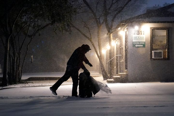 Two people play in the snow in San Antonio, Sunday, Feb. 14, 2021. (AP Photo/Eric Gay)