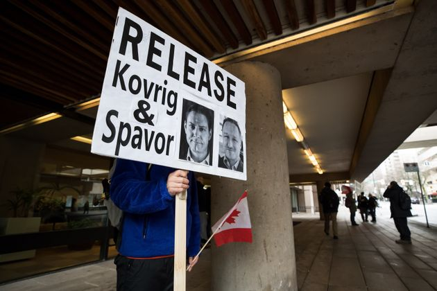 A young man holds a sign bearing photographs of Michael Kovrig and Michael Spavor on Jan. 21,