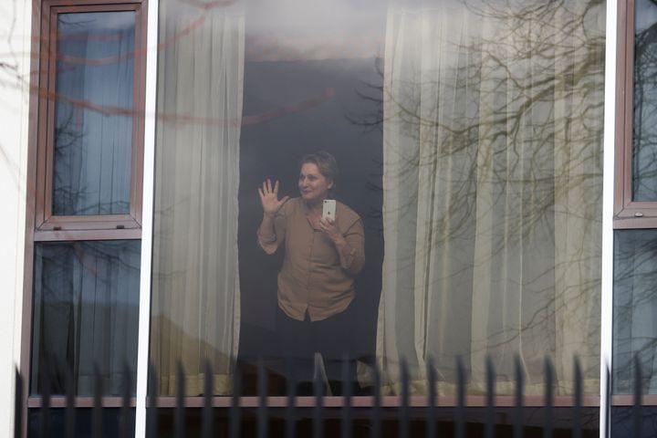 Zari Tadayon gestures from a window of the Radisson Blu Hotel.