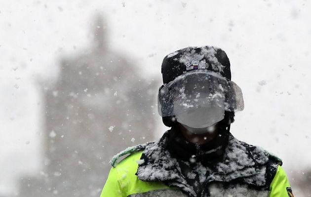 자료사진. 대설주의보가 발효된 28일 오전 서울 종로구 광화문광장을 지나는 한 경찰관의 안면보호 페이스쉴드에 눈이 덮혀 있다.