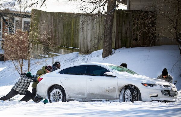 East Austin residents push a car out of the snow on Monday.