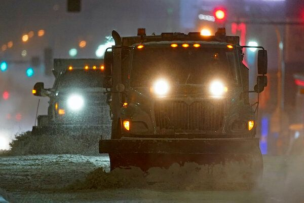 Snow plows clear a street in Kansas City, Mo., as temperatures drop below 0 degrees Fahrenheit on Monday.