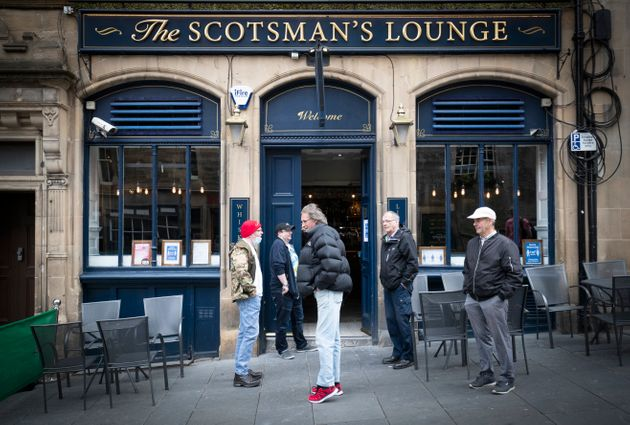 People wait for opening outside The Scotsman's Lounge pub in