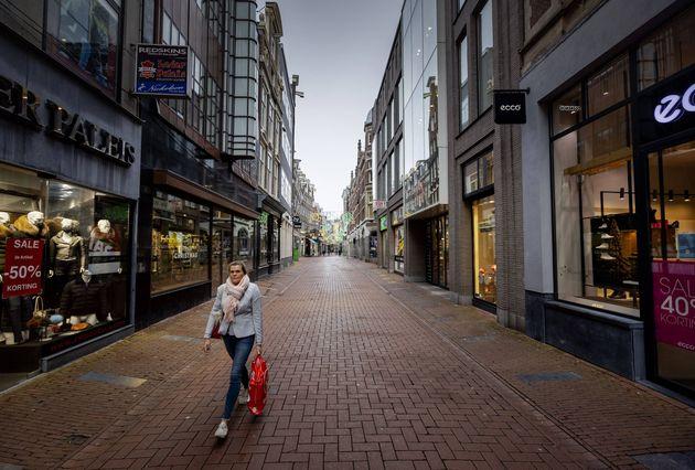 Une passantes dans les rues d'Amsterdam vides le 15 décembre 2020 (Photo by ROBIN VAN LONKHUIJSEN / ANP...