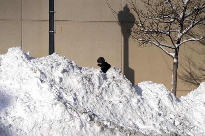 A man walks past mounds of plowed snow from nine consecutive days of measurable and fresh fallen snow Tuesday, Feb. 16, 2021,