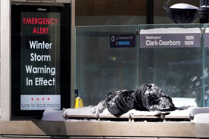 A homeless man Tuesday, Feb. 16, 2021, sleeps at the Chicago Transit Authority's Clark & Dearborn bus station, the morning af