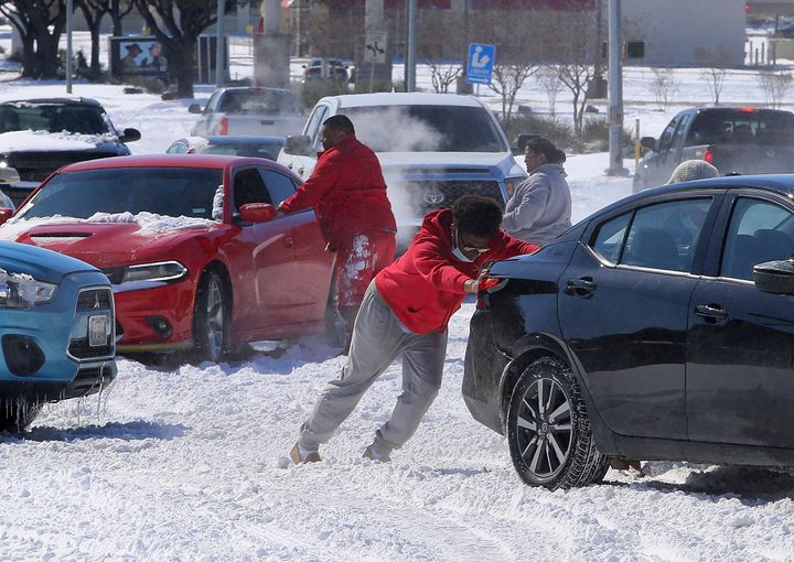 People push a car free after spinning out in the snow Monday, Feb. 15, 2021 in Waco, Texas. (Jerry Larson/Waco Tribune-Herald
