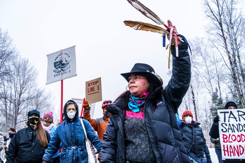 A Native American environmental activist dances with an eagle feather in front of the construction site for Enbridge's Line 3