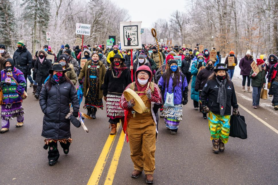Environmentalists and Native American activists march to the construction site for the Line 3 oil pipeline near Palisade, Min