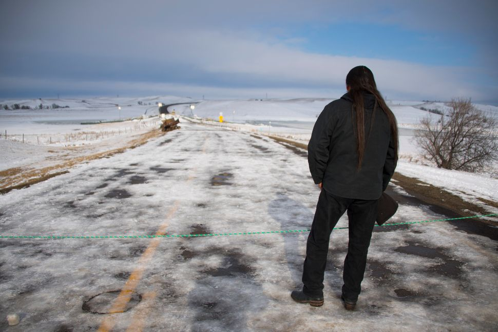 Activist Pete Sands of the Navajo Nation looks out over an area set as a borderline where the police guard a bridge near Ocet
