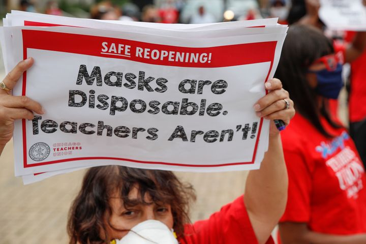 A woman holds a sign during the Occupy City Hall Protest and Car Caravan hosted by Chicago Teachers Union in Chicago, Illinoi