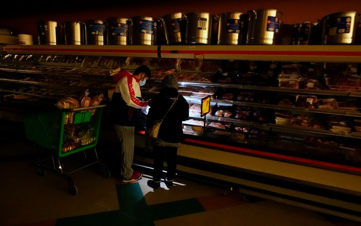 Customers use the light from a cellphone to look in the meat section of a Dallas grocery store on Feb. 16. Though the store lost power, it was open for cash-only sales.