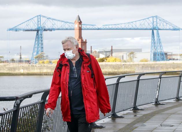 A man wearing a face mask walks by the Tees Transporter Bridge in Middlesbrough last