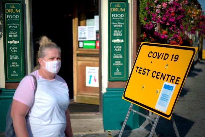 Pedestrians wearing a facemask walking past a sign for a Covid-19 test centre in Leyton, east London