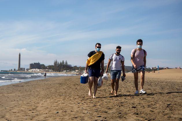 Jóvenes con mascarilla en la playa de Maspalomas en Gran Canaria, el 23 de enero de