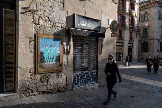 Una mujer pasa por delante de un grafiti de 'Las tres vacunas', del artista TVBoy en Plaza de Sant Jaume