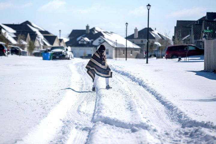 A man walks to his friend's home in a neighborhood without electricity as snow covers the BlackHawk neighborhood in Pfl