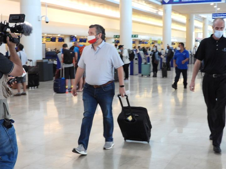 Sen. Ted Cruz (R-Texas) checks in Thursday for a flight at Cancun International Airport after backlash over his family's geta