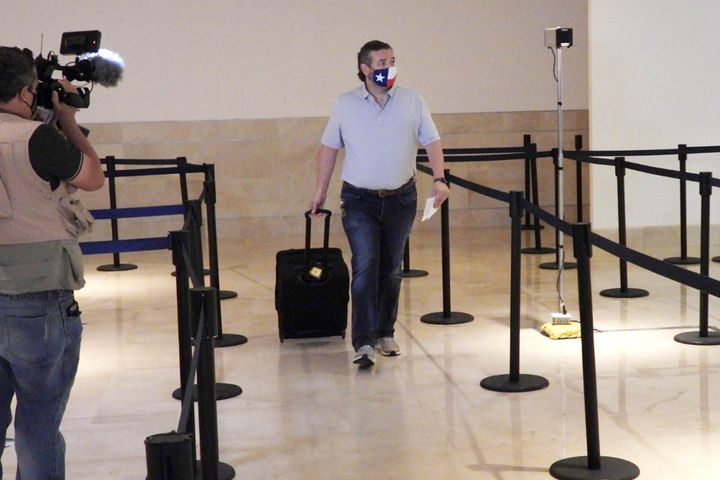 Sen. Ted Cruz checks in for his flight at Cancun International Airport on Thursday.