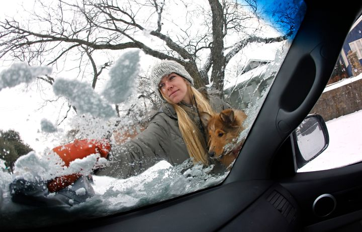 Caroline Marlett holds her dog Kit while scraping the snow off her car after a snow storm on Feb. 17 in Fort Worth, Texas.