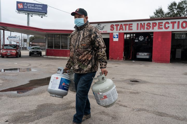 A person carries empty propane tanks, bringing them to refill at a propane gas station after winter weather caused electricity blackouts on Feb. 18 in Houston, Texas. Winter storm Uri brought severe temperature drops causing a catastrophic failure of the power grid in Texas.