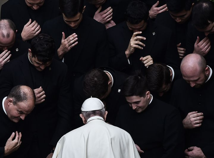 Pope Francis prays with priests at the end of a limited public audience at the San Damaso courtyard in The Vatican on Septemb