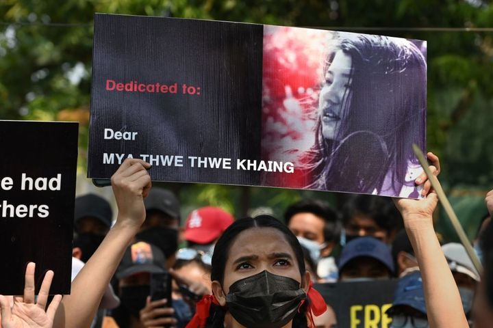 A protester holds up a poster with a portrait of Mya Thwate Thwate Khaing who died from a gunshot wound after being shot in t