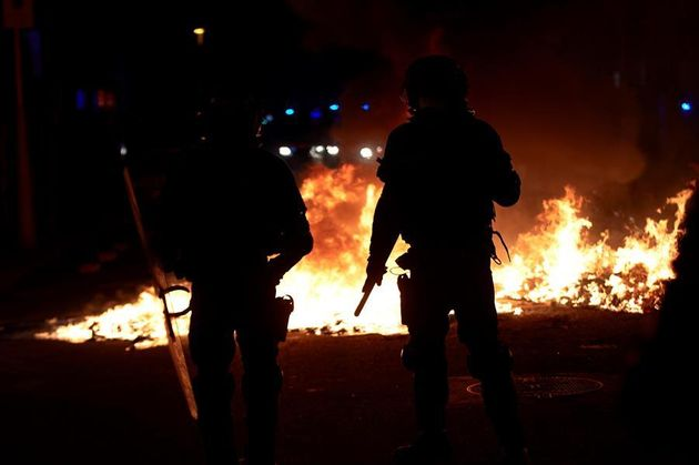Agentes de los Mossos junto a una barricada en llamas en la Calle Aragó este jueves en las protestas...