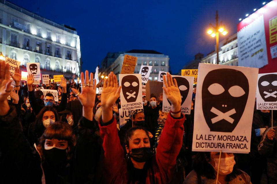 Supporters of Catalan rapper Pablo Hasel hold signs during a protest against his arrest in Madrid, Spain,...
