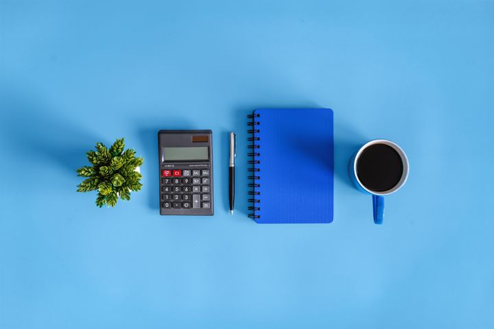 Coffee Break. Calculator and Notebook on Blue Desk