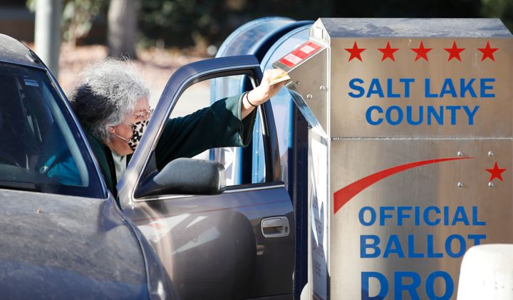 A voter drops off her mail in ballot at a dropbox at the Salt Lake County election office in Salt Lake City, Utah, on Oct. 29