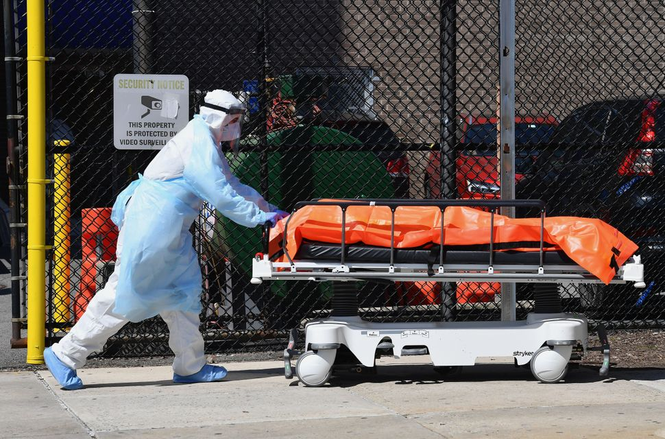 A staff member at the Wyckoff Heights Medical Center in New York moves a body to a refrigerated truck on April 2, 2020,