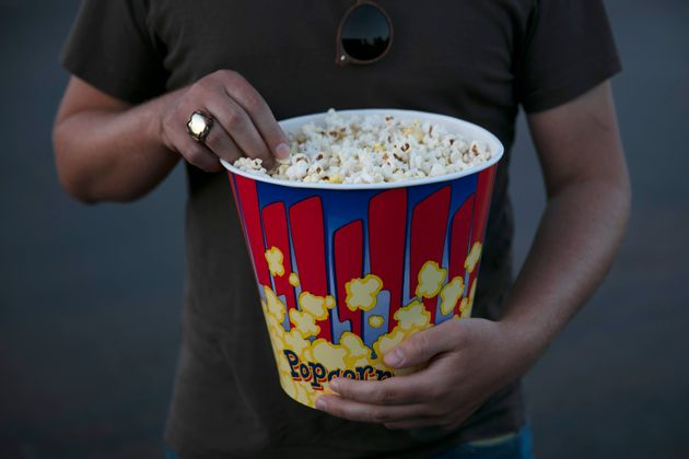 File photo of a moviegoer eats popcorn at Mission Tiki drive-in theater in Montclair, Calif. on May 28,