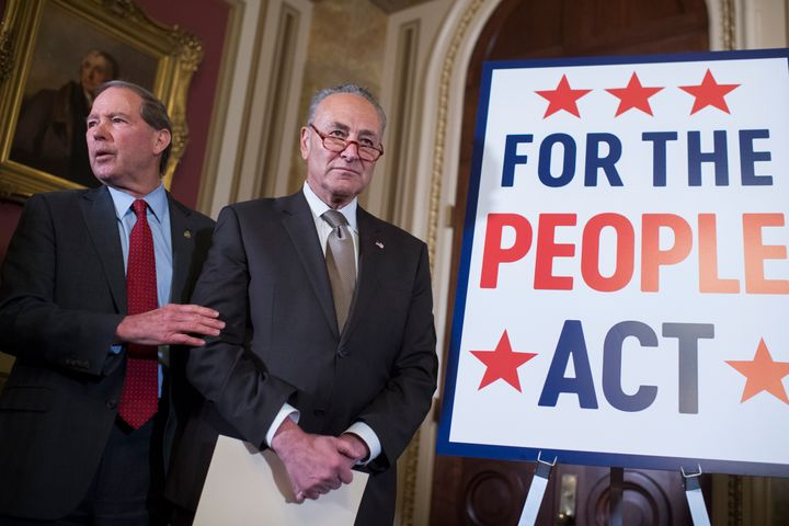 Then-Senate Minority Leader Charles Schumer (center) and then-Sen. Tom Udall (D-N.M.) attend a news conference about the For the People Act on March 27, 2019, in the U.S. Capitol.