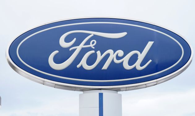 The Ford company logo is viewed on a sign outside a dealership on Dec. 20,