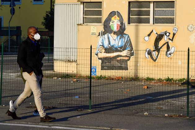 People walk near a mural celebrating nurses in Codogno, one year after the small northern town became...