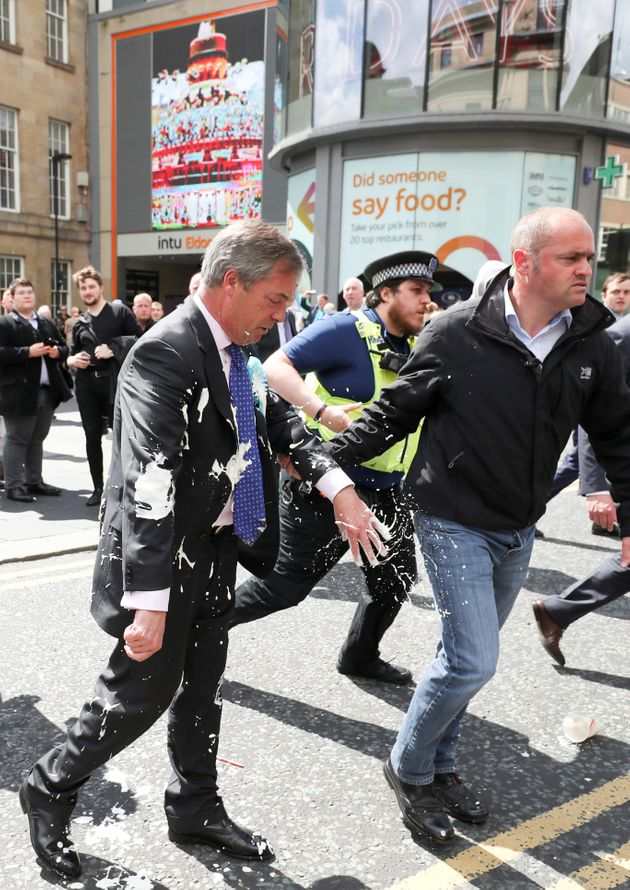 Brexit Party leader Nigel Farage gestures after being hit with a milkshake while arriving for a Brexit...