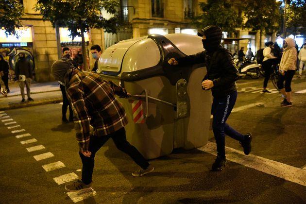 Unos manifestantes mueven un contenedor en Barcelona para hacer una