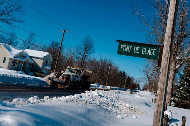 Un chasse-neige passe devant un panneau indiquant la route de glace reliant les villes de Pointe-Fortune...