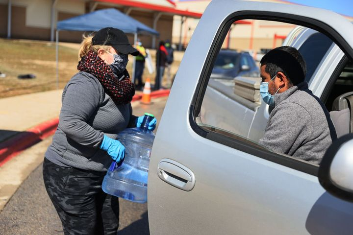 KYLE, TEXAS - FEBRUARY 20: Erin Purdy gives Domingo Ibarra a water jug at a drive through water distribution center setup at