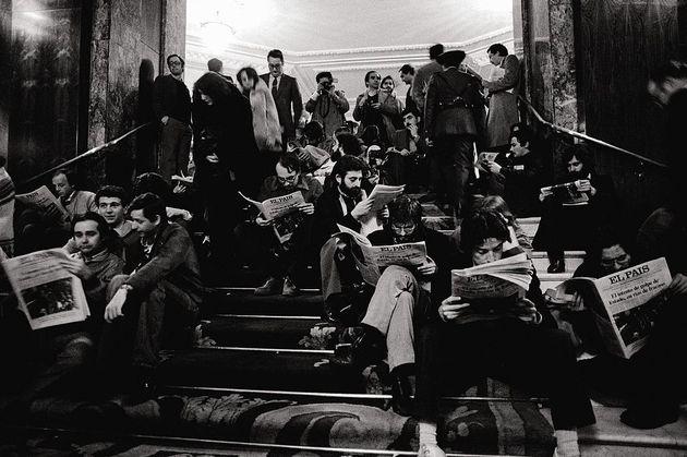 Un grupo de periodistas lee la edición especial del periódico 'El País' en las escaleras...